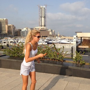 A texting roller blader on the marina in Beirut with the new Citadelle skyscraper in the background.